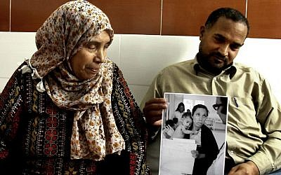 In this Tuesday, May 13, 2014 photo, Palestinian refugees Fathiyeh Sattari, 62, and her son Hassan, 40, look at their photograph that was taken at the Rafah UN Relief and Works Agency, UNRWA, clinic in 1975. (photo credit: AP/Adel Hana)