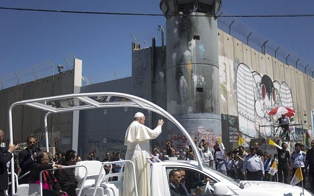 Pope Francis waves as he rides on a vehicle passing by Israel's security barrier on his way to a mass in Manger Square next to the Church of the Nativity, traditionally believed to be the birthplace of Jesus Christ in the West Bank town of Bethlehem on Sunday, May 25, 2014.  (Photo credit: AP/Ariel Schalit)