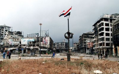Two Syrian national flags hang on a pole as government officials inspect damages in the city of Homs, Syria, on May 8, 2014. (photo credit: AP)