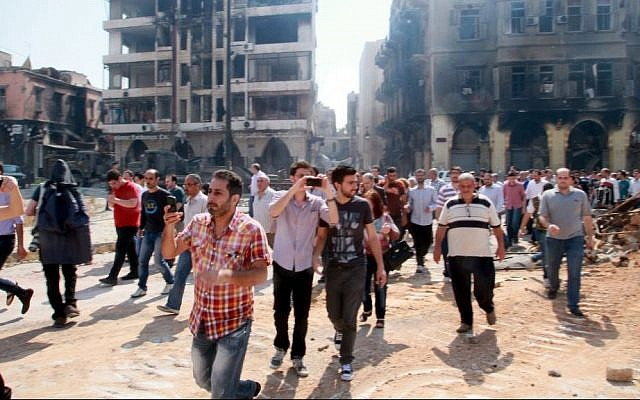 In this photograph made on a government-led media tour, Syrian civilians return to Homs, Syria on Friday, May 9, 2014, where bulldozers cleared rubble from the streets of battle-scarred districts in the central Syrian city. (AP Photo)