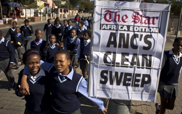 Schoolchildren walk past a newspaper placard reporting the election victory of Jacob Zuma's African National Congress (ANC) party, based on preliminary results, on Friday (photo credit: AP/Ben Curtis)