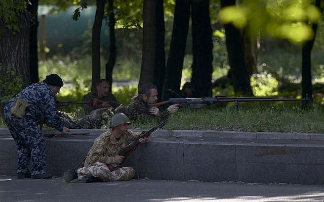 Pro-Russian insurgents aim their rifles during fighting around the airport outside Donetsk, Ukraine, Monday, May 26, 2014. (photo credit: AP/Vadim Ghirda)