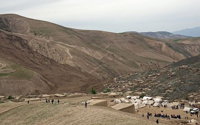 Survivors walk near the site of Friday's landslide that buried Abi-Barik village in Badakhshan province, northeastern Afghanistan, Sunday, May 4, 2014. (Photo credit: AP/Massoud Hossaini)