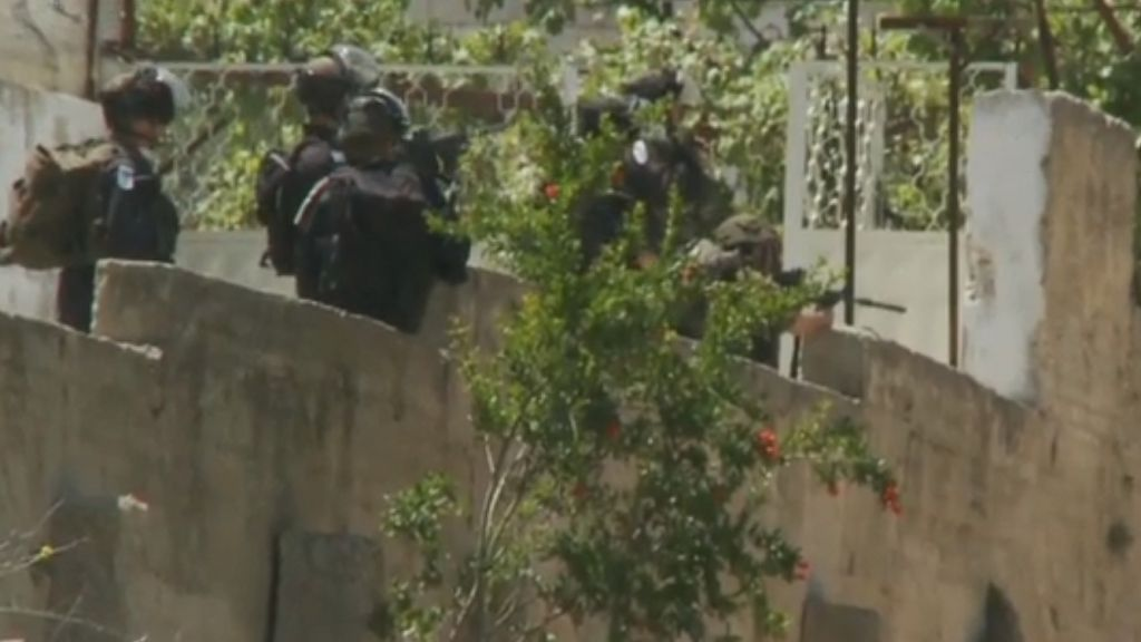 An IDF soldier is seen pointing his rifle at a group of Palestinians during a Nakba Day demonstration in the West Bank town of Bituniya on May 15. The soldier has been suspended from his unit and is under investigation. (screen capture: CNN)