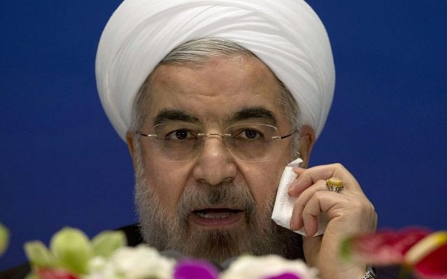 Iranian President Hassan Rouhani wipes his cheek as he speaks during a press conference at a hotel in Shanghai, China, on Thursday, May 22, 2014. (photo credit: AP Photo/Ng Han Guan)