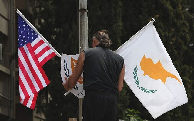 A municipality worker places a US flag, left and Cypriot flag, on an electricity column, on a street in divided capital Nicosia, Cyprus, Tuesday, May 20, 2014. (photo credit: AP/Petros Karadjias)