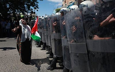 Palestinian police with riot gear stand guard as they stop supporters of the Popular Front for the Liberation of Palestine (PFLP) from reaching the headquarters of PA President Mahmoud Abbas in the West Bank city of Ramallah on September 7, 2013, during a protest against negotiations with Israel (photo credit: Issam Rimawi/Flash90)