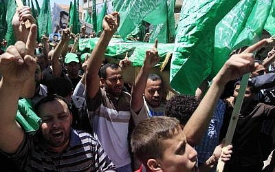 Palestinian mourners wave the green flag of the Islamist movement Hamas at a funeral on April 30, 2014, in the West Bank city of Ramallah. (photo credit: Issam Rimawi/Flash90)