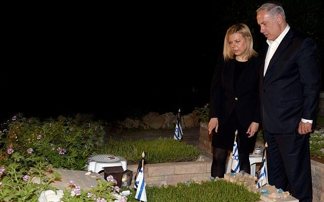 Prime Minister Benjamin Netanyahu and his wife Sara seen next to the grave of Netanyahu's late brother Yoni at the Mt Herzl military cemetery in Jerusalem, on the eve of Israeli Memorial Day, May 3, 2014. Yoni Netanyahu, an elite commando, was killed in action during Operation Entebbe by Ugandan soldiers when Israeli special forces carried out a famed rescue operation after an aircraft hijacking in July, 1976. (Photo credit: Haim Zach/GPO/Flash90)