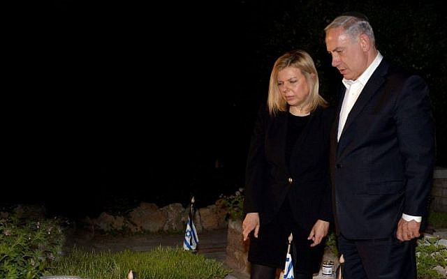 Prime Minister Benjamin Netanyahu and his wife Sara seen next to the grave of PM Netanyahu's late brother Yoni at the Mt Herzl military cemetery in Jerusalem, on the eve before Israeli Memorial Day. (photo credit: Haim Zach/GPO/Flash90)