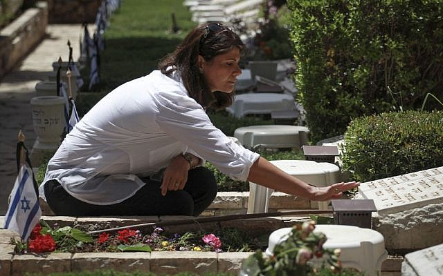 A woman who works at the Mount Herzl Military Cemetery checks the grave of Tzion Tayeb, who the military said had died in the Yom Kippur War in 1973, on Sunday, May 4, 2014, on the eve of the Israeli Remembrance Day. The deceased soldier's family said they dug up the grave last Friday only to find it empty. They had decided to open the grave because they claimed that the State had misidentified his body. The case is currently under investigation. (Photo credit: Hadas Parush/Flash 90)