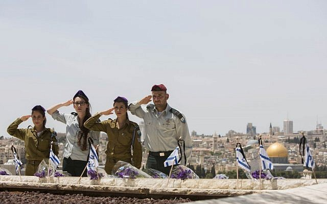 Israeli soldiers place the flag on the grave of fallen soldiers during a ceremony held at the Mount of Olives in preparation for Memorial Day. May 4, 2014. (photo credit: Yonatan Sindel/Flash90)