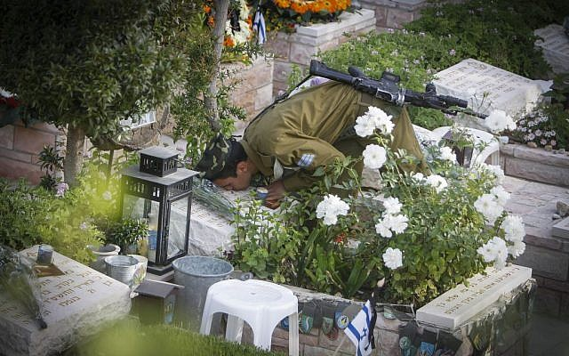 An Israeli soldier kisses the grave of a fallen soldier at the Mt Herzl military cemetery in Jerusalem on May 05, 2014. (Photo credit: Miriam Alster/Flash90)