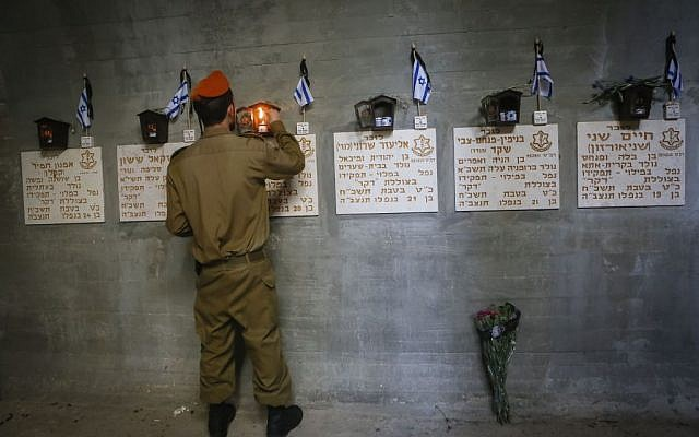 An Israeli soldier lights candles next to the names of Israeli fallen soldiers at the Dakar submarine monument, at the Mt Herzl military cemetery in Jerusalem on May 05, 2014. (Photo credit: Miriam Alster/Flash90)