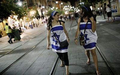 Young women wrapped in Israeli flags walking the streets of Jerusalem as Israel's celebrates its 66th Independence Day on May 05, 2014. (Photo credit: Miriam Alster/FLASH90)