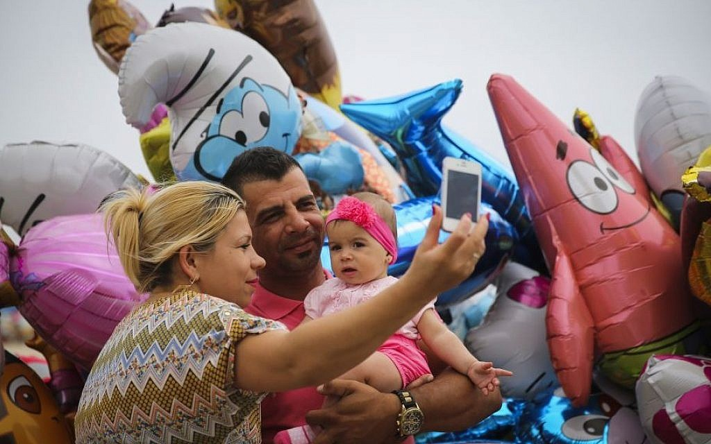 A family take a selfie on the Tel Aviv beach boardwalk. (illustrative photo credit: Hadas Parush/Flash 90)