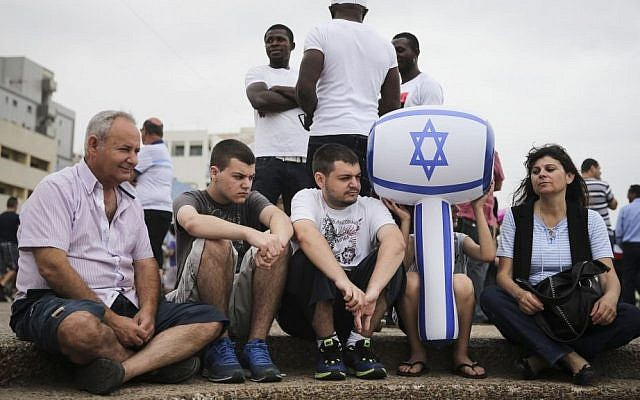 Israelis sit by the Tel Aviv beach boardwalk as they wait for the military airshow on Israel's 66rh Independence Day, Tuesday, May 6, 2014. (photo credit: Hadas Parush/Flash 90)