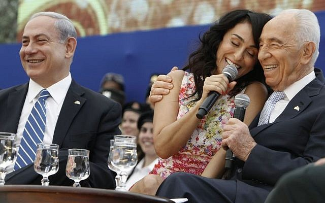 Then-President Shimon Peres (R) and Prime Minister Benjamin Netanyahu sing along with Iranian-born singer Rita as they participate in a ceremony for outstanding soldiers as part of Israel's 66th Independence Day celebrations, at the President's residence in Jerusalem, Tuesday, May 06, 2014. (photo credit: Miriam Alster/Flash90)