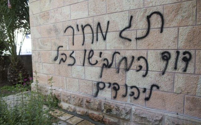 "Anti-Christian graffiti reading ""Price tag, David the king, Jesus Junk for the Jews"" spray painted on the Romanian Church in Jerusalem on May 9, 2014. (Photo credit: Yonatan Sindel/Flash90)"