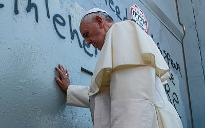 Pope Francis prays against the security barrier at Bethlehem, May 25, 2014 (photo credit: Nour Shamaly/Flash90)