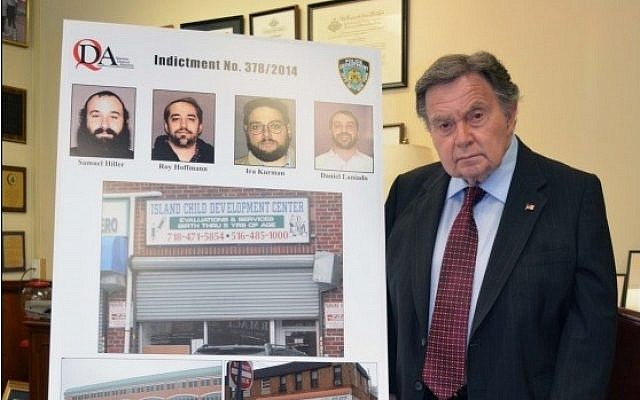 Queens District Attorney Richard A. Brown stands next to pictures of the 4 men indicted for stealing from a Far Rockaway special needs school  (photo credit: Courtesy/Queens District Attorney)