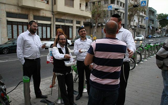 Dosim volunteers distribute matzo balls outside of Army Radio (photo credit: Dosim/Courtesy)