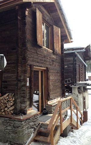The log cabins date back to earlier times in Saas Fee, once used to store crops, and are slowly being restored, like this one that is being used as a fondue cafe (photo credit: Jessica Steinberg/Times of Israel)