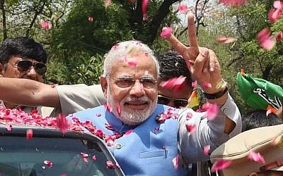 Supporters shower flower petals on opposition Bharatiya Janata Party (BJP) leader and India's next prime minister Narendra Modi as he arrives at the party headquarters in New Delhi, India, Saturday, May 17, 2014. (Photo credit: AP)