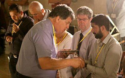 Vicar Pileggi giving communion to participants in the conference (photo credit: Carino Casas/ Christ Church Jerusalem)