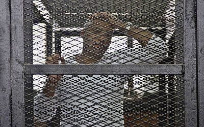 Canadian-Egyptian acting Al-Jazeera bureau chief Mohammed Fahmy appears in a defendant's cage in a courthouse near Tora prison along with other defendants during a trial on terror charges in Cairo, Egypt, Saturday, May 3, 2014. (photo credit: AP/Hamada Elrasam)
