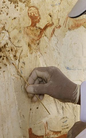 An Egyptian conservator works at the site of a newly-discovered tomb dating back to around 1100 B.C. at the Saqqara archaeological site, 30 kilometers (19 miles) south of Cairo, Egypt, Thursday, May 8, 2014.  (photo credit: AP Photo/Amr Nabil)