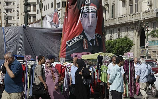 Egyptians walk past a banner with a portrait of Egyptian Presidential hopeful Abdel-Fattah el-Sissi at a market in Cairo, Egypt, Saturday, May 17, 2014. El-Sissi faces leftist Hamdeen Sabahi, who has the support of youth groups who led the 2011 uprising against autocrat Hosni Mubarak. El-Sissi, who led the July 3, 2013 overthrow after millions protested against Islamist President Mohammed Morsi, is widely expected to win the May 26-27 vote on a wave of nationalistic, anti-Islamist fervor. (photo credit: AP/Amr Nabil)