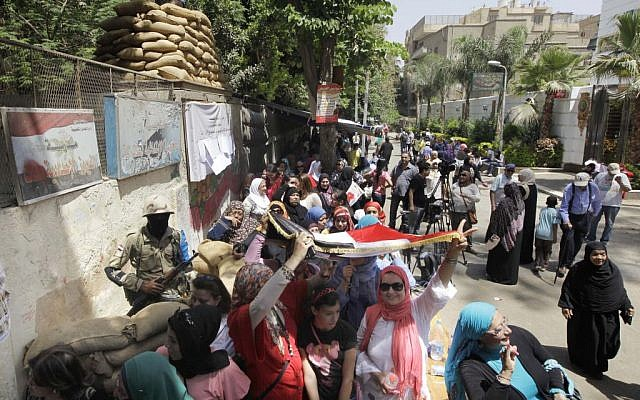 Voters line up as some take shade under a national flag outside a polling station to vote for president in an election that comes nearly a year after the military's ouster of the nation's first freely elected president, the Islamist Mohammed Morsi in Cairo, Egypt, Monday, May 26, 2014. (photo credit: AP Photo/Amr Nabil)