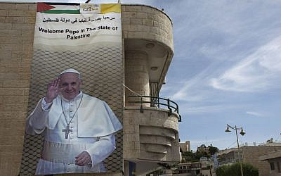 In this photo taken Monday, May 19, 2014, a welcome banner for Pope Francis with his picture hangs on a building in the West Bank city of Bethlehem. (photo credit: AP/Nasser Nasser)
