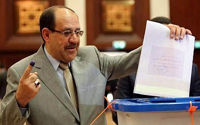 Iraqi Prime Minister Nouri al-Maliki prepares to cast his vote at a polling station in the heavily fortified Green Zone in Baghdad, Iraq, on Wednesday, April 30, 2014. (photo credit: AP Photo)