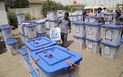 Electoral workers carry ballot boxes at a counting center in Basra, Iraq's second-largest city, May 1, 2014 (photo credit: AP/Nabil Al-Jurani)