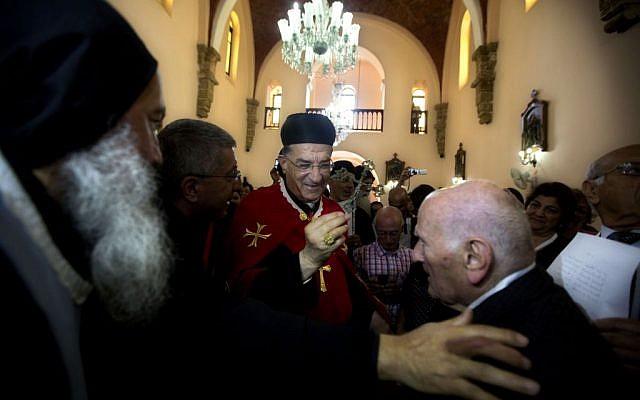 Cardinal Bechara Rai, head of the Maronite Catholic Church, center, visits a church in Jaffa, a mixed Jewish and Arab neighborhood in Tel Aviv, Israel, Monday, May 26, 2014.  (photo credit: AP Photo/Sebastian Scheiner)