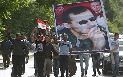 Syrian citizens who live in Lebanon shout slogans and carry a big portrait of Syrian President Bashar Assad, as they walk towards to the Syrian Embassy to ballot their vote for their presidential elections, in Baabda, east of Beirut, Lebanon, Wednesday May 28, 2014. (photo credit: AP/Hussein Malla)