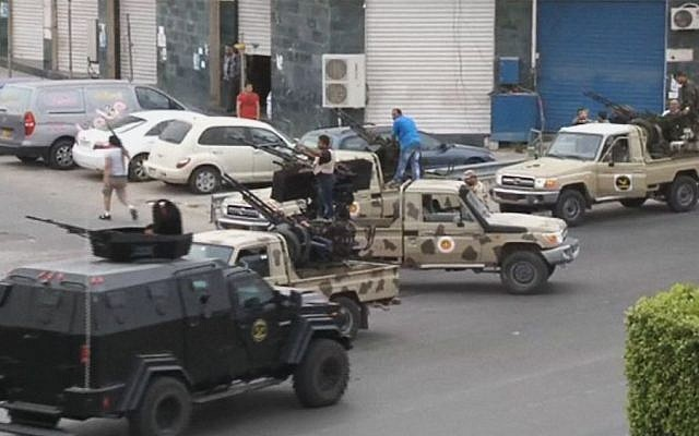In this image made from video provided by the Libyan national army via AP Television, Tripoli joint security forces on vehicles with heavy artillery stand guard on the entrance road to the parliament area after troops of Gen. Khalifa Hifter targeted Islamist lawmakers and officials at the parliament in Tripoli, Libya, Sunday, May 18, 2014. Forces loyal to a rogue Libyan general attacked the country's parliament Sunday, expanding his eastern offensive against Islamists into the heart of the country's capital. (photo credit: AP Photo/Libyan national army)