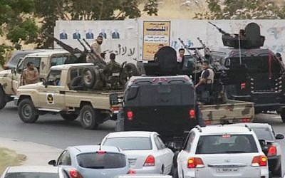 In this image made from video provided by the Libyan national army via AP Television, vehicles with heavy artillery of the Tripoli joint security forces move closer to the parliament building after troops of Gen. Khalifa Hifter targeted Islamist lawmakers and officials at the parliament in Tripoli, Libya, on May 18, 2014.  (Photo credit: AP/Libyan national army/file)