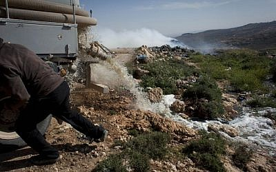 A Palestinian driver of a wastewater suction container vehicle, that is rented by locals to vacuum their house's underground wastewater storage containers, disposes his vehicle's load of sewage on top of a hill at the outskirts of the Palestinian village of Silwad, adjacent to the Israeli settlement of Ofra, north of the West Bank city of Ramallah, April 17, 2014 (photo credit: AP/Nasser Nasser)