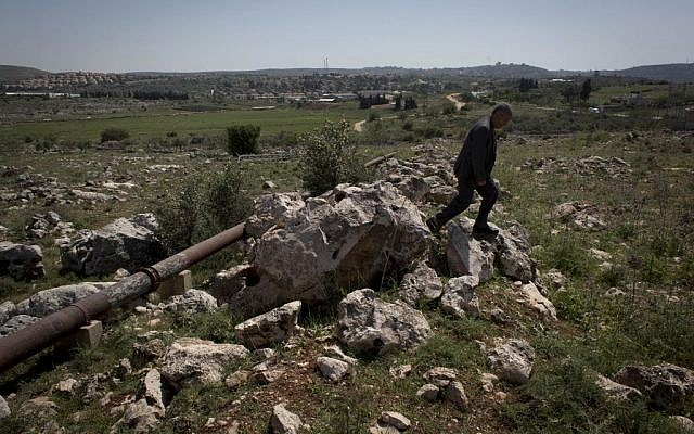 In this April 17, 2014 photo, Abdel Rahman Saleh, the mayor of the Palestinian village of Silwad, inspects his village's land dedicated by the Israeli settlement of Ofra, seen in the background, for an illegal wastewater treatment plant, north of the West Bank city of Ramallah. (photo credit: AP/Nasser Nasser)