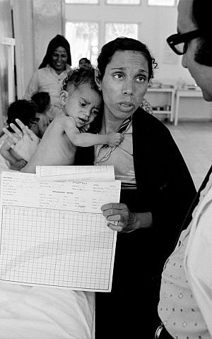 In this 1975 photo, Fathiyeh Sattari, a worried Palestinian mother talks to a doctor about her underweight child, Hassan, who is being treated at a Rafah health center run by the UNRWA. (photo credit: AP/G.Nehmeh/UNRWA Photo Archives)