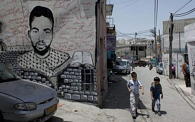 Two Palestinian school children walk past a mural depicting late Palestinian activist Ahmed Mosleh, who was killed during an Israeli army operation in 2006, with his name in Arabic and the names of other killed Palestinians, in an alley of the Dheisheh Palestinian refugee camp, in the West Bank city of Bethlehem, on Tuesday, May 20, 2014. (photo credit: AP Photo/Nasser Nasser)