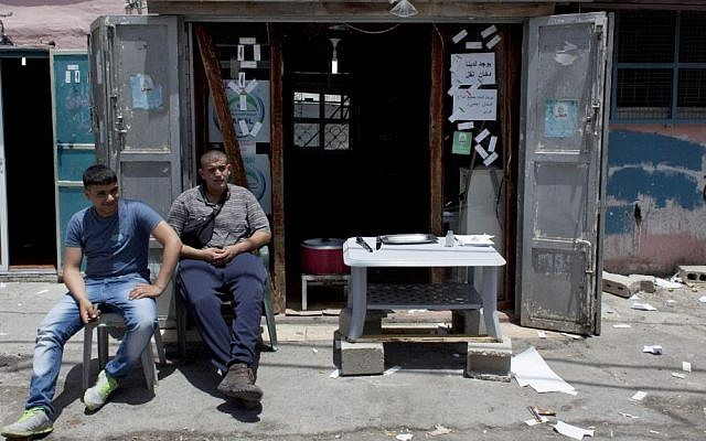 Two Palestinian vendors wait for customers in front of their tobacco shop, in an alley of the Dheisheh Palestinian refugee camp, in the West Bank city of Bethlehem, on Tuedsay, May 20, 2014. (photo credit: AP Photo/Nasser Nasser)