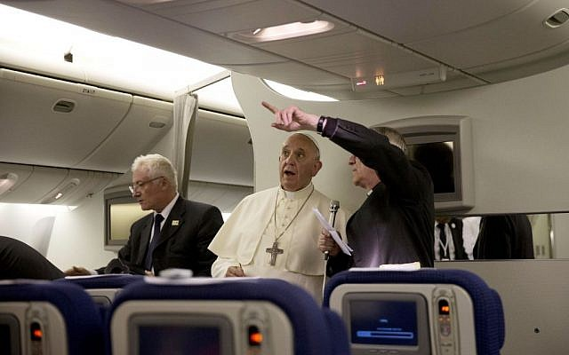Pope Francis talks talks with Vatican Spokseman Father Federico Lombardi, right, during a press conference he held aboard the papal flight on his way back to Rome at the end of a three day trip to the Midle East, Monday, May 26, 2014 (photo credit: AP /Andrew Medichini, Pool)