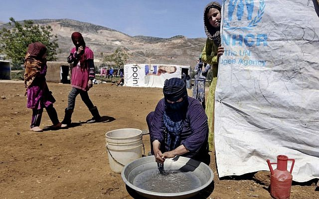 In this Tuesday, April 29, 2014 photo, Halbiya, 50, who fled her home from Deir al-Zour, washes her hands after working on a field, at a Syrian refugee camp, near the eastern town of Kab Elias, Lebanon. (photo credit: AP/Bilal Hussein)
