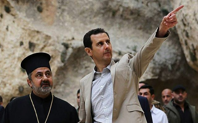 In this Sunday, April 20, 2014 file photo, released by the Syrian official news agency SANA, Syrian President Bashar Assad, right, visits the Christian village of Maaloula, near Damascus, Syria. (photo credit: AP/SANA, File)
