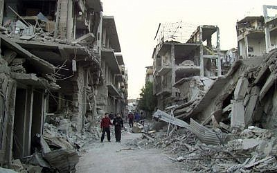 This file photo, released on Thursday November 29, 2012, shows Syrian citizens walking in a destroyed street that was attacked by Syrian forces warplanes, at Abu al-Hol street in Homs province, Syria. (photo credit: AP/Homs City Union of The Syrian Revolution, File)