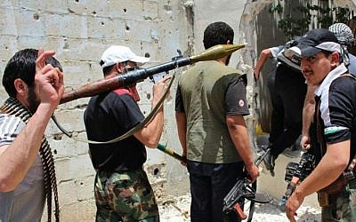Syrian rebels of unknown affiliation hold their weapons as they prepare to fight against Assad regime troops in Homs province, June 18, 2012 (photo credit: AP/File)